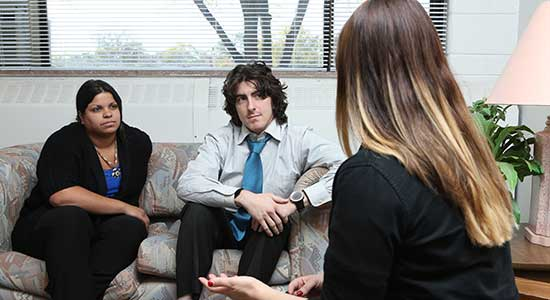 photo of a male/femle couple on the couch speaking with a counselor